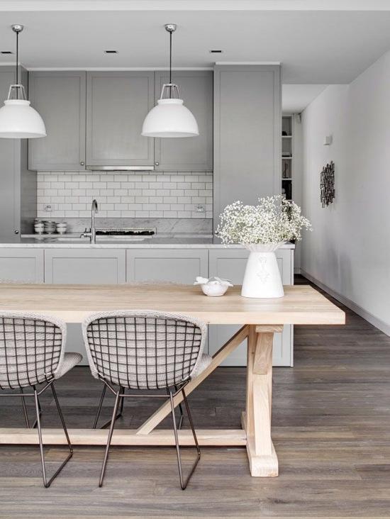 Nowoczesna szara kuchnia z drewnianym stołem  zdjęcie w