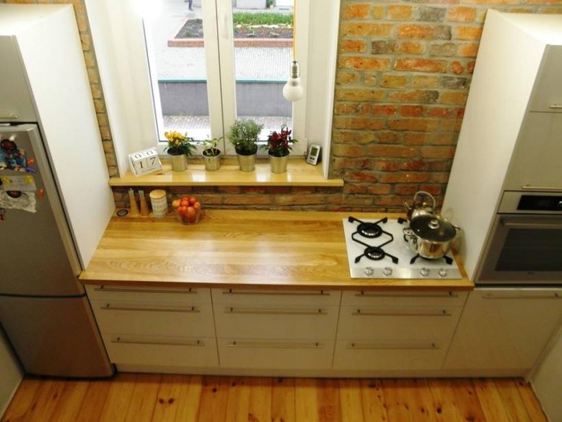 Biała kuchnia z drewnianym blatem na tle czerwonych   -> Kuchnia Z Cegiel