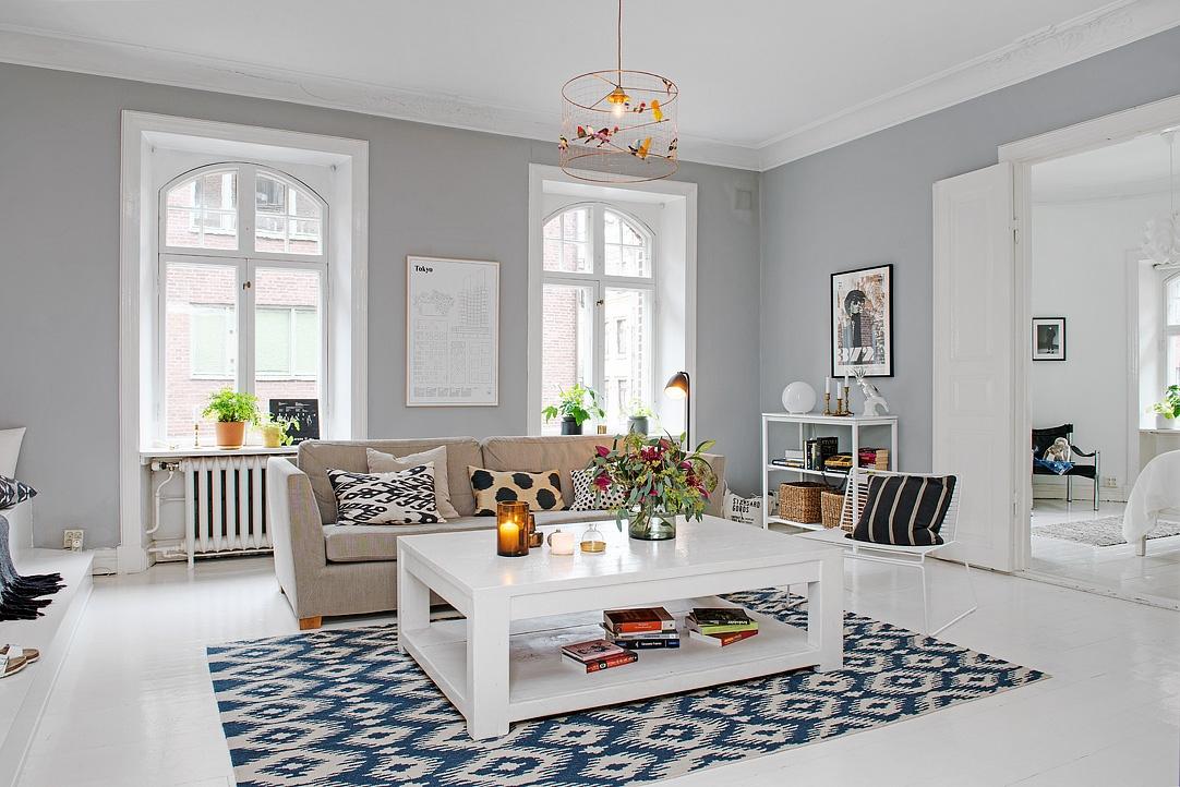 Biały stolik kawowy z półka,beżowa sofa,niebiesko-biały dywan i szare ściany w aranżacji salonu skandynawskiego