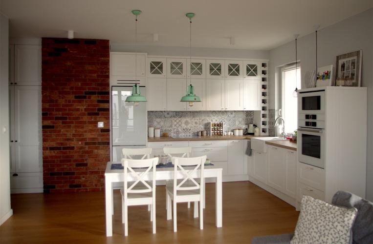 Przyjemna aranżacja kuchni z jadalnią naszej czytelniczki, z białymi szafkami i panelem z czerwonych cegieł