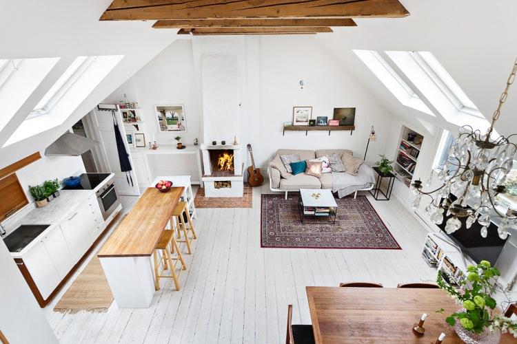 Aranżacja mieszkania na otwartej przestrzeni ze skośnymi sufitami i białą drewnianą podłogą
