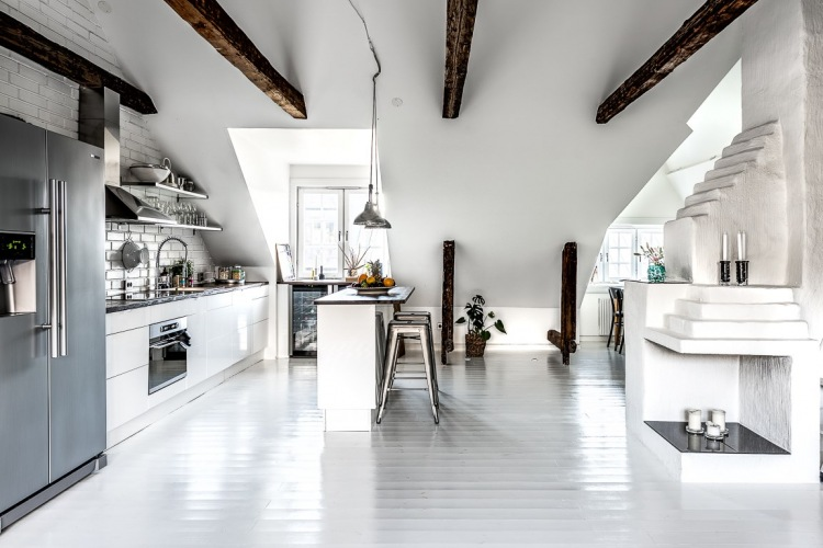 Chłodna aranżacja białego mieszkania na poddaszu z drewnianymi belkami