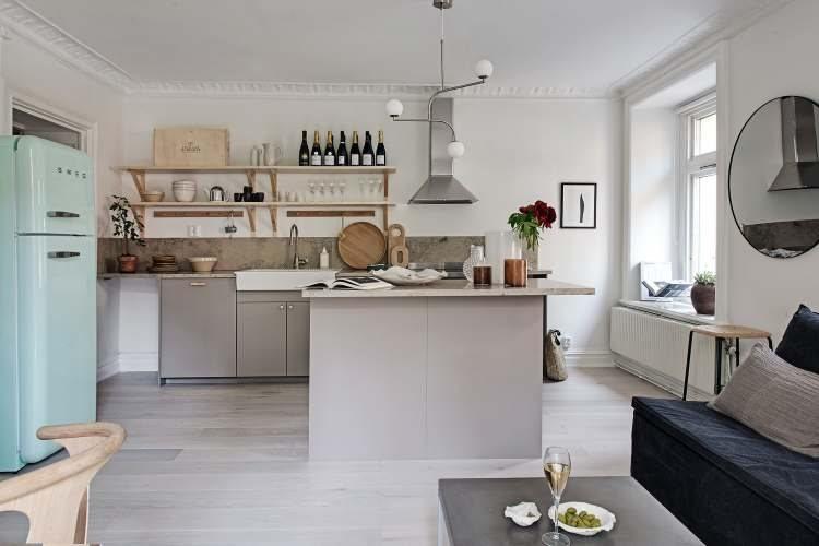 Pomysł na aranżację mieszkania z błękitną lodówką w otwartej kuchni i bardzo małą sypialnią