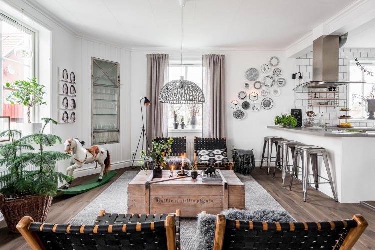 Oryginalna aranżacja mieszkania z drewnianymi meblami w salonie oraz białą kuchnią