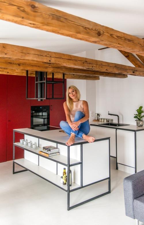 Oryginalna polska aranżacja mieszkania na poddaszu z drewnianymi belkami i akcentami w czerwieni