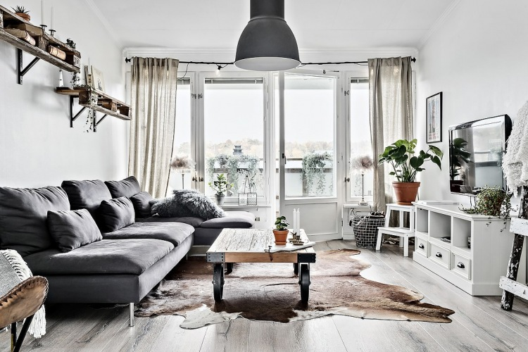 Aranżacja szarego mieszkania w kamienicy z drewnianą podłogą i eklektycznymi dodatkami