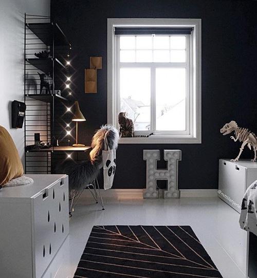 Ciekawa aranżacja domu z białą podłogą i kuchnią z czarnymi szafkami z drewna