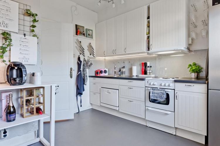 Romantyczna aranżacja kawalerki w białym kolorze z sypialnią na antresoli
