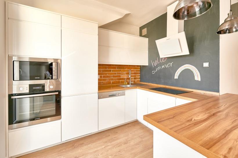 Biała Kuchnia Z Drewnem I ścianą Z Farbą Tablicową Zdjęcie