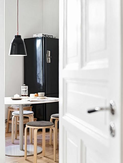 Drewniane stołki i czarna lodówka z lampą w kuchni