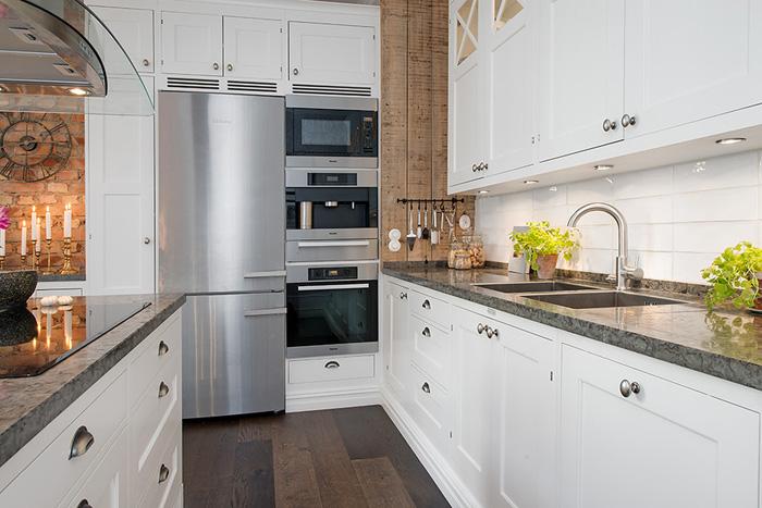 Skandynawska biała kuchnia ze ścianami z desek  zdjęcie w