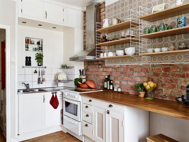 Mała biała kuchnia z drewnianym blatem i ścianą  zdjęcie w serwisie Lovingit   -> Kuchnia Biale Cegly