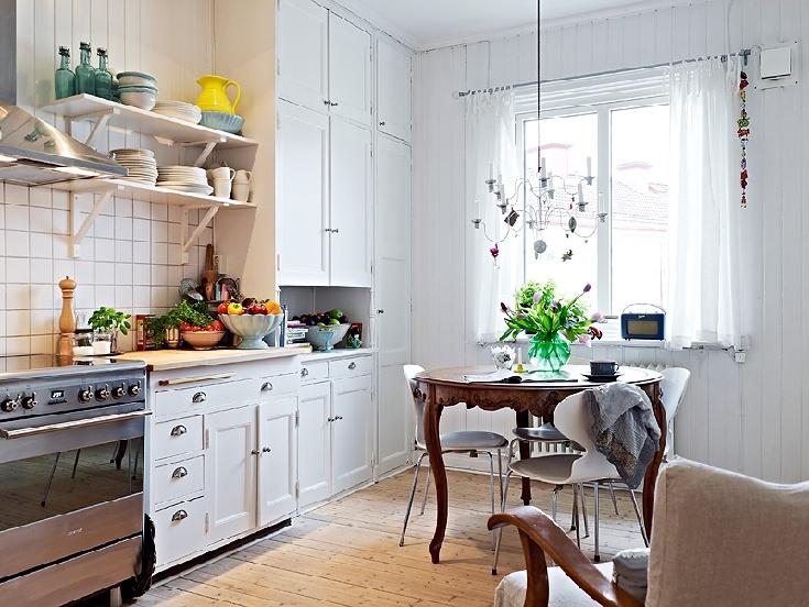 Brązowy, okragły stylizowany stół w białej kuchni