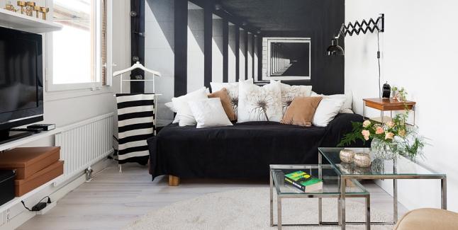 Czarna sofa z białymi i jasno-brązowymi poduszkami ...