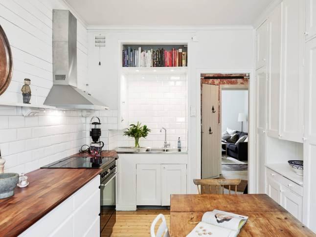 Mała Biała Kuchnia Z Drewnianymi Blatami I Stołem Zdjęcie